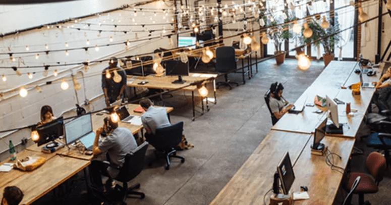 kancelarijski prostor sa dugačkim stolovima i dosta stolica
